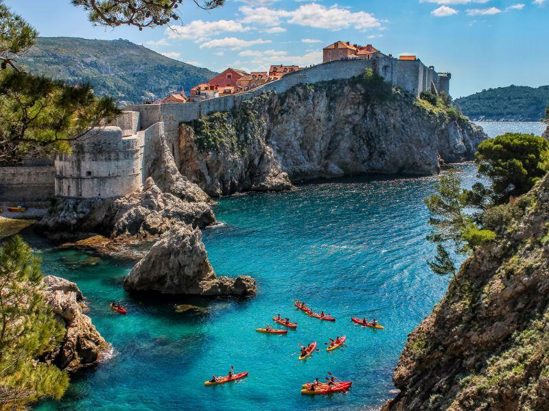 Blick auf die Stadtmauer von Dubrovnik und eine Gruppe von Seglern.